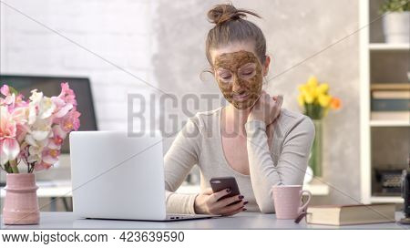 Woman cosmetic facial skin care. Woman in skin rubber peeling face beauty mask sitting at desk using phone and laptop.