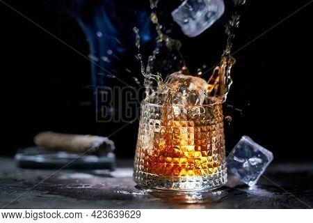 Icecube splashing to glass of whiskey. Copy space, black background. Smoking cigar and whiskey, brandy, cognac, alcoholic drink .