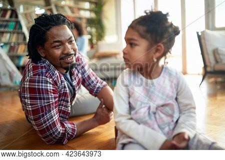 A young father is full of emotions while playing with his daughter in a family atmosphere at home. Family, together, love, playtime