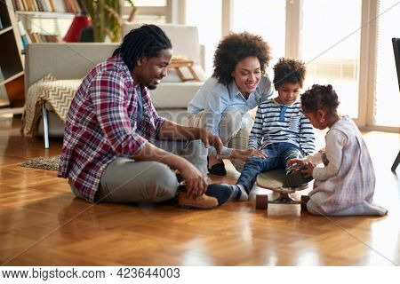 A happy parents playing with their kids on the floor in a cheerful atmosphere at home. Family, together, love, playtime