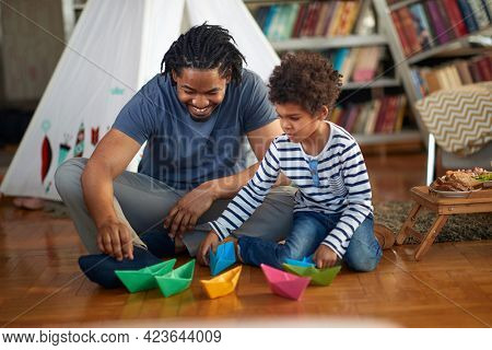 Father and son playing with paper boats on the floor in a relaxed atmosphere at home. Family, together, love, playtime