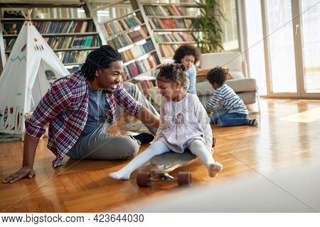 A little daughter enjoys playing with her father in a relaxed atmosphere at home. Family, together, love, playtime