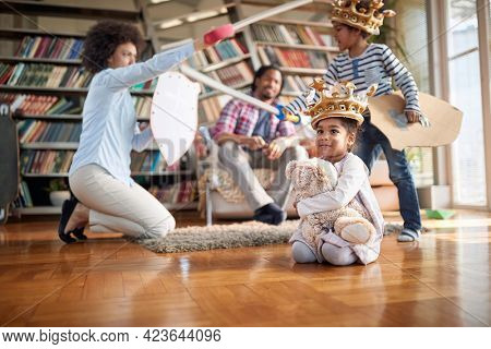 A young cheerful family enjoying a playtime in a playful atmosphere at home together. Family, together, love, playtime