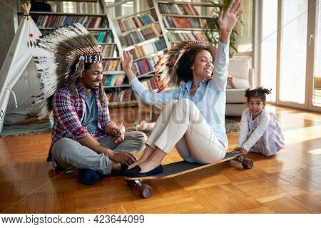Young cheerful parents with indian headdresses have a wonderful time with their little daughter in a playful atmosphere at home. Family, together, love, playtime