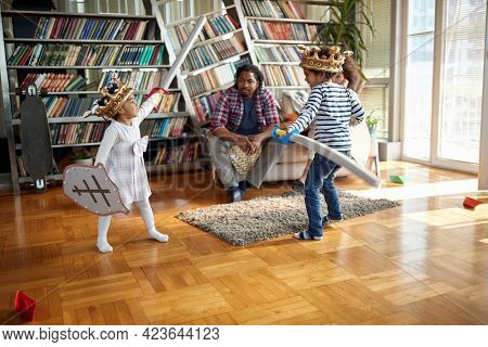 Kids with swords and shields playing and spending quality time with their parents in a cheerful atmosphere at home. Family, together, love, playtime