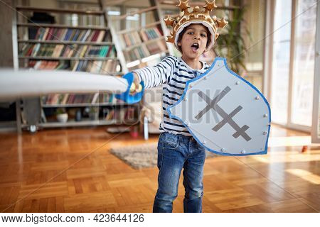 A cute little knight boy who shouts and attacks while posing for a photo in a playful atmosphere at home. Family, together, love, playtime