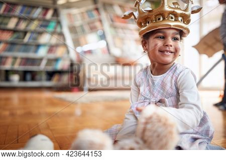 A cute little girl with sweet smile is full of joy while playing in a family atmosphere at home. Family, together, love, playtime