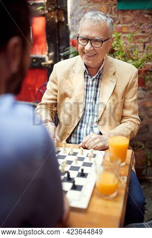 senior good looking caucasian male looking at his younger opponent playing chess , sitting in outdoor cafe