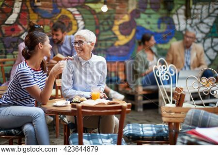 two females, different ages, sitting in outdoor cafe, talking, smiling, drinking coffee, looking each other. healthy relationship between young adult and elderly persons