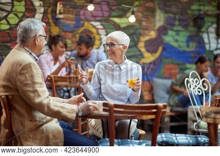 elderly caucasian couple talking in outdoor cafe, smiling, drinking coffee and juice. long term marriage concept