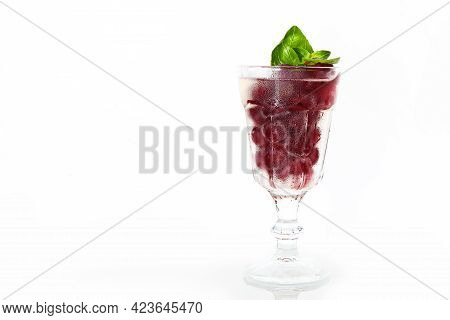 Red Berry With Basil Leaves In A Glass Glass. Basil Leaves. Cherry Lemonade In A Transparent Glass.