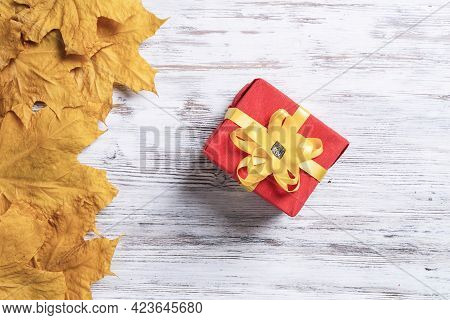 Bright Autumn Composition With Gift Box And Yellow Maple Leaves. Holiday Present Decorated Yellow Ri
