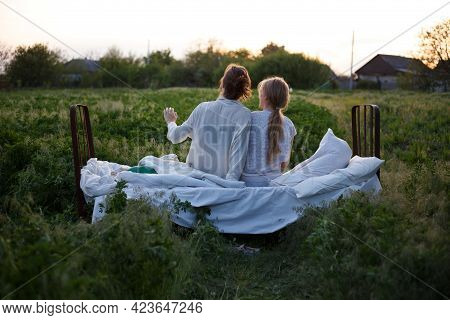 Girls Sit  On The Bed In A Green Field. Healthy Sleep In Nature. Ecotourism