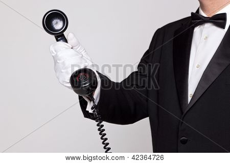 Butler holding the handset from a telephone