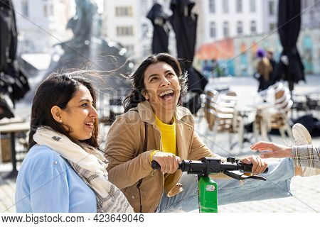 Lifestyle Portrait Of A Two Asian Young Girl Friends On The Electro Scooter Having Fun In A European