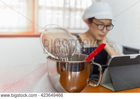 Selected Focus Of Bakery Equipment With Woman Baker Working On Laptop In Background.