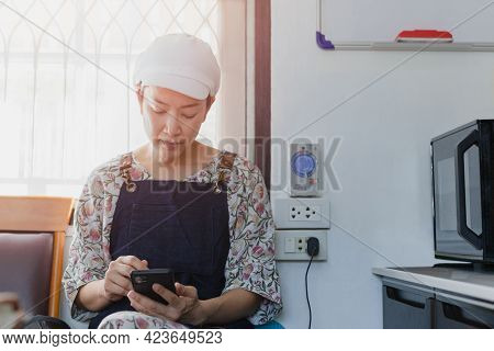 Woman Baker Sitting On The Chair Using Smartphone At The Kitchen