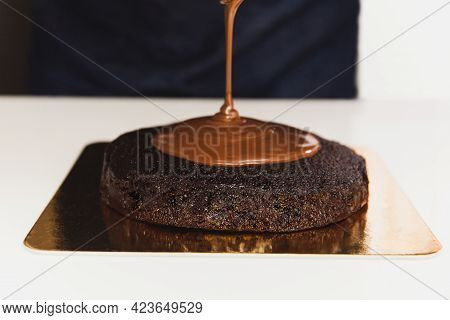 Chef Pouring Ganache On Top Of Chocolatecake