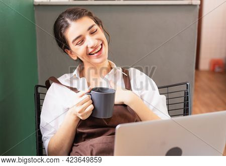 Beautiful Caucasian Barista Woman Sits Relaxing With Coffee Break And Happy On Online Video With Fri