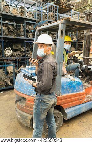 Men Work Together, Wear Safety Facemask, Use Walkie-talkie. Caucasian Engineer Man Wear Safety Facem