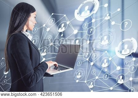 Attractive European Businesswoman Using Laptop In Blurry Office With Abstract Social Network Hologra