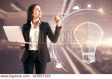 Happy White Woman With Laptop And Abtsract Glowing Polygonal Light Bulb Interface On Blurry Office B