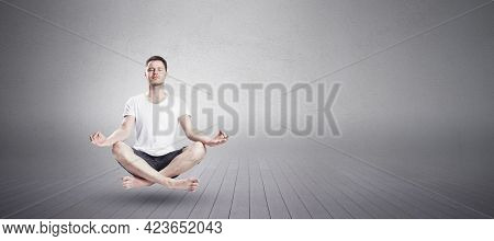 Man Sitting In Yoga Lotus Position With Closed Eyes In Fitness Studio. Relaxation And Meditation Con