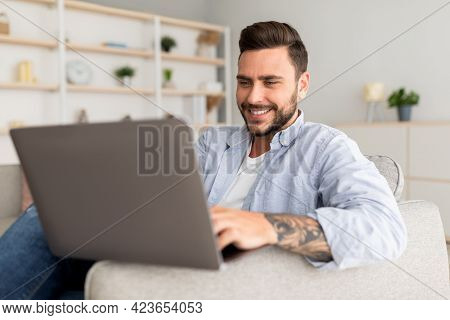 Modern Job Lifestyle. Happy Tattooed Man Sitting On Sofa At Home And Working On Laptop