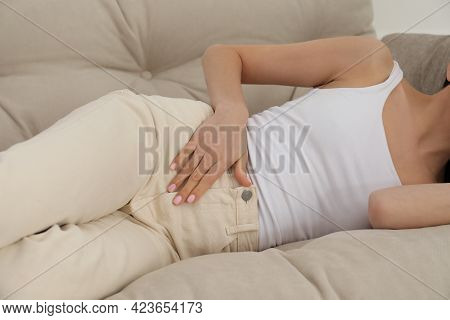 Woman Suffering From Appendicitis Inflammation On Sofa Indoors, Closeup