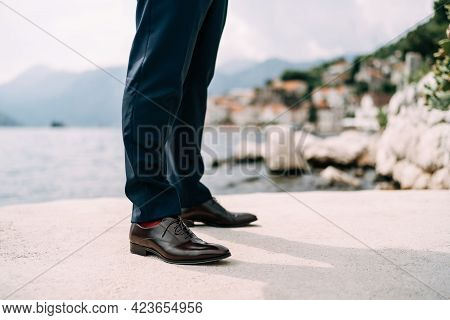 Legs Of A Man In Blue Pants, Red Socks And Brown Shoes Standing On The Pier, Close-up
