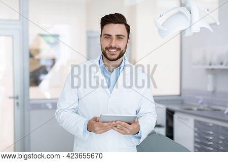 Delighted Dentist Smiling And Holding Digital Tablet In Dental Cabinet