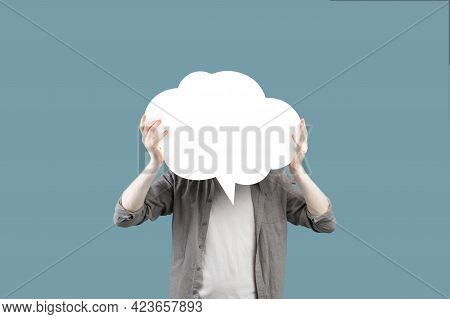 Unrecognizable Young Albino Man Holding Blank Speech Bubble In Front Of His Face Over Turquoise Stud