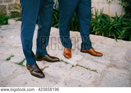 The Legs Of Two Men Standing On A Cobbled Road, Close-up. The Groom And His Best Man During The Prep