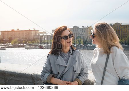 Two Young Women Talking Outdoors. Joyful Friends Standing Against The Backdrop Of The City And Telli