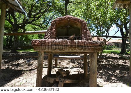 Clay Oven On Wooden Table With Native Trees From The Region In The Background, Oven Widely Used To M