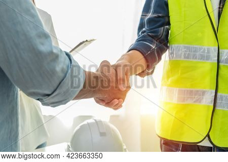 Contractor. Construction Worker Team Hands Shaking After Plan Project Contract On Workplace Desk In