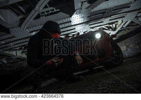 Drug Dealer Making Phone Call To His Fellow Gang Members While Staying Under The Iron Train Bridge D
