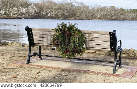 A Bench Facing The Lake At Belmond State Park With A Christmas Wreath Placed On The Back For The Hol