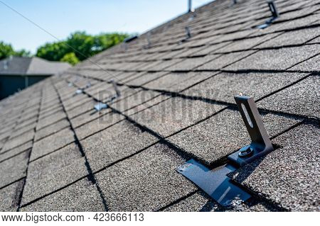 Residential Asphalt Shingle Roof With Metal Anchors Installed For The Installation Of A Solar Panel