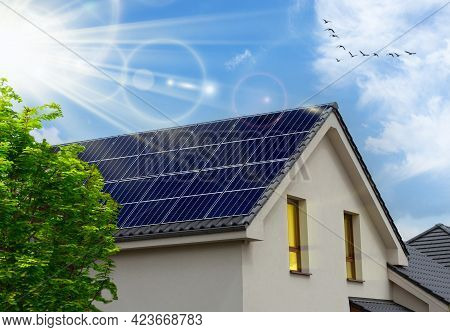 Solar Panel On A Roof Reflecting The Sun And The Cloudless Blue Sky.