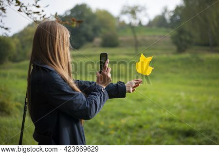 Woman Holds A Yellow Maple Leave At Arm's Length In Autumn Park. Maple Leave In A Woman's Hand Glow