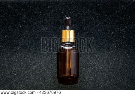 Serum Bottle On Black Stone Background. Essential Oil, Fluid, Extract Or Skincare Serum Close Up.