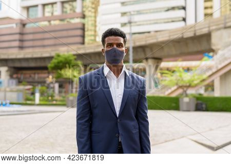 Portrait Of African Businessman Wearing Face Mask Outdoors In City
