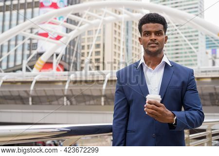 Portrait Of African Businessman Outdoors Holding Take Away Coffee Cup
