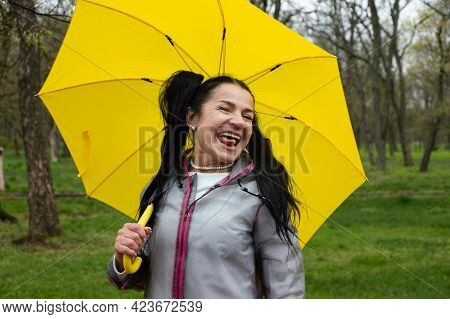 Happy Senior Cheerful Mature, Elderly, Retired Woman With Yellow Umbrella Enjoying Life At Rainy Day