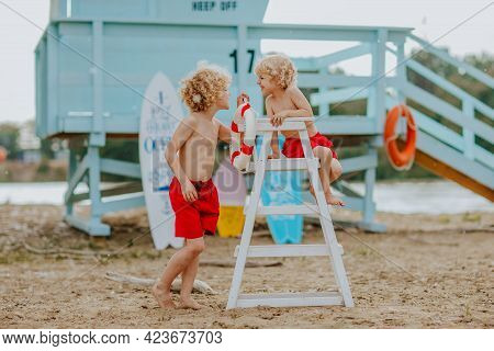 Two Blond Curly Boys In Red Shorts Playing On The Sand Beach With Blue Lifeguard Tower, High White C