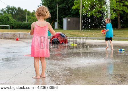 Small Children Playing With Water And Toys At Splash Pad In The Local Public Park During Hot Summer