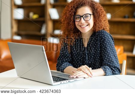 Ambitious Atractive Redhead Female Entrepreneur Looks At The Camera With A Friendly Toothy Smile, Yo