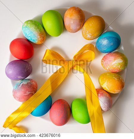Colored Eggs For Easter On A White Background Spread Out In A Circle Surrounded By Colored Ribbons.