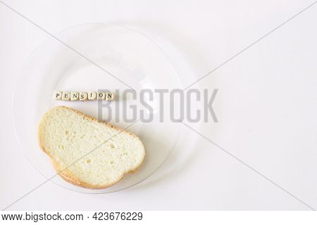 Piece Of Bread In A Transparent Plate Next To The Inscription Pension. Minimum Pension And Old Age P